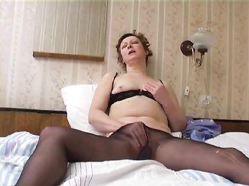 Сольная мастурбация взрослой одинокой женщины в капронках на кровати
