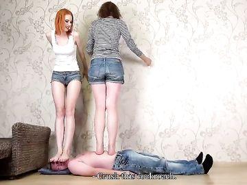 Две высокие стройные девушки топчат ногами по послушного чувака