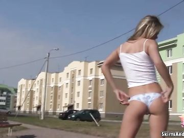 Игривая девушка раздевается в общественном месте и показывает тело