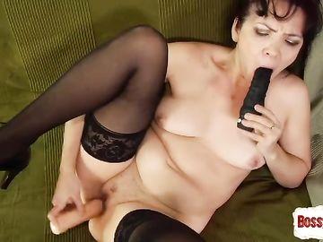 Женщина в возрасте засовывает игрушку для взрослых во влагалище