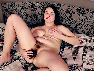 Сексапильная взрослая брюнетка в спальне резиновым членом ласкает киску