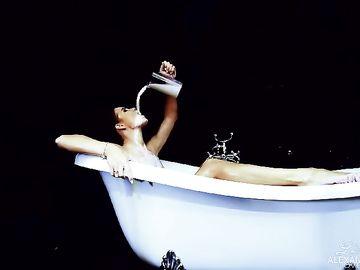 Голая красотка в ванной обливает тело молоком и сексуально позирует